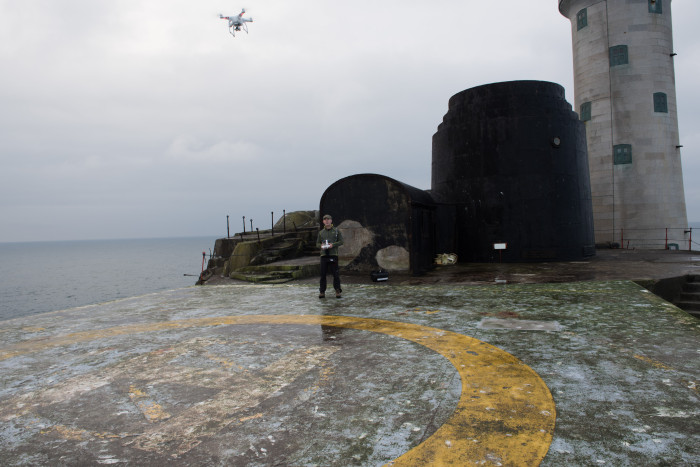 A person stood on a helipad by the coast flies a drone.